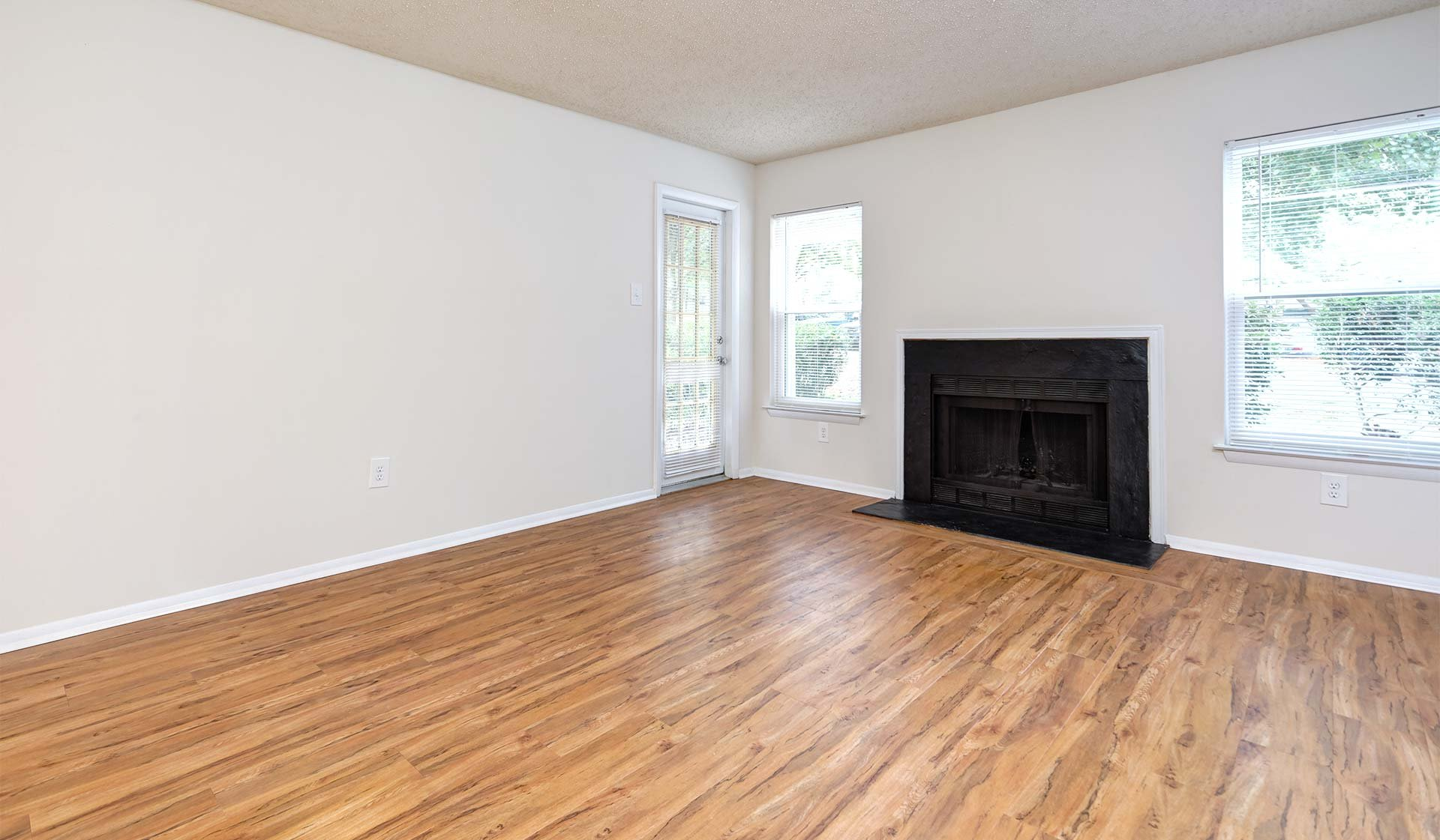 Burke Shire Commons Apartments - Empty Room with hardwood floors and black fireplace - Burke, Virginia