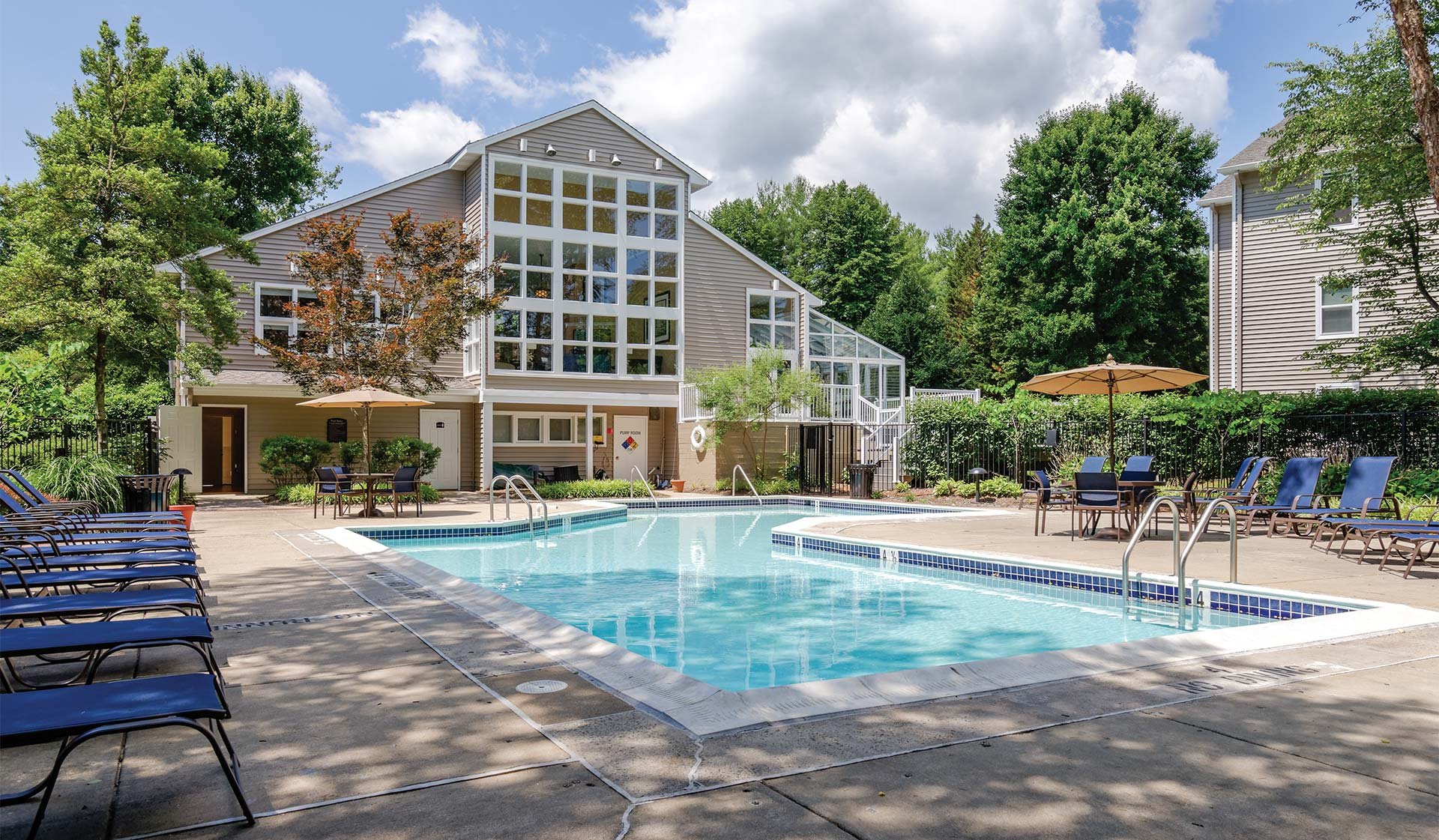 Burke Shire Commons Apartments - View of pool surrounded by chairs with clubhouse in background - Burke, Virginia